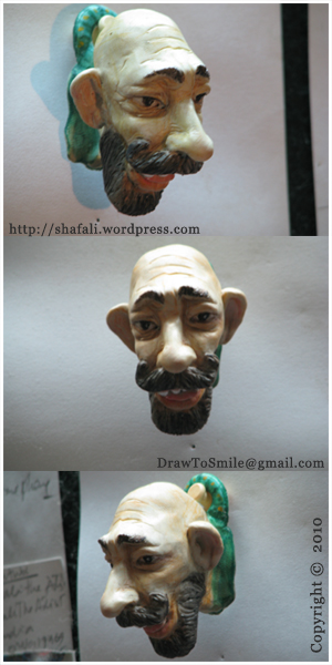 3d caricature cartoon clay sculpture (wall plaque) of a smiling bald man with moustache and beard.